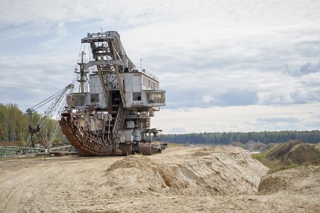 Escalier mécanique rouillé dans le sable le jour d'été contre ciel nuageux