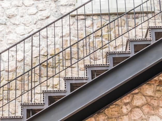 Escalier en métal et mur de pierre