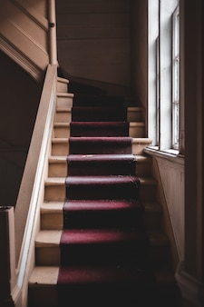 Escalier rouge et marron près de la fenêtre