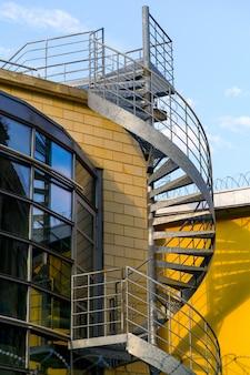 Escalier de secours en spirale grise sur un bâtiment en fil de fer barbelé