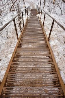 Escaliers en métal rouillé qui descendent, marches et mains courantes en fer rouillé