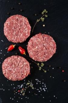Escalope de burger de viande crue fraîche sur la planche d'ardoise noire avec des herbes et des épices. copiez l'espace, vue de dessus. mise au point sélective.