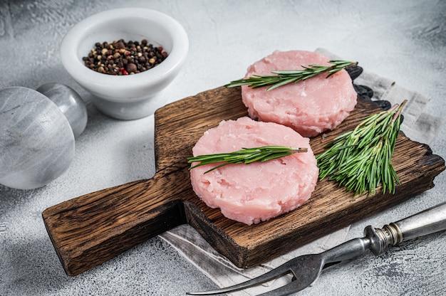 Escalope de galette de viande hachée crue non cuite aux herbes. fond blanc. vue de dessus.