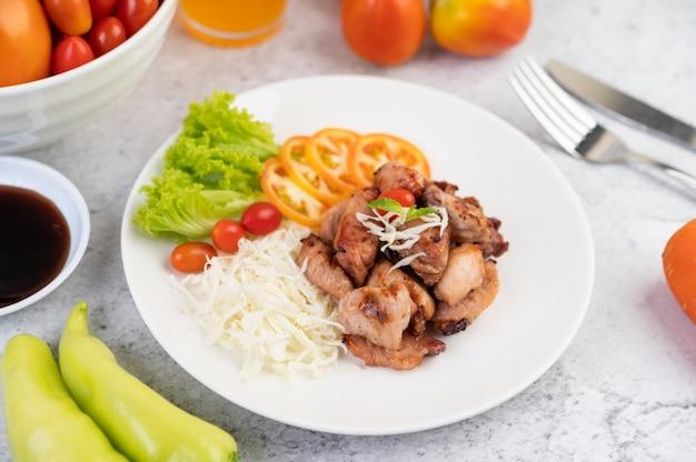 Escalope de porc grillée avec tomates et salade, disposée dans un plat blanc.