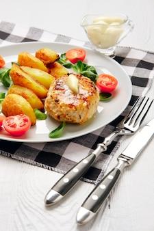 Escalope de poulet frit avec des tranches de pommes de terre servies avec une salade de tomates cerises et de maïs.