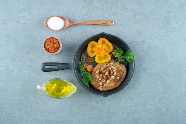 Escalope de poulet sur une poêle noire avec de l'huile et du sel.