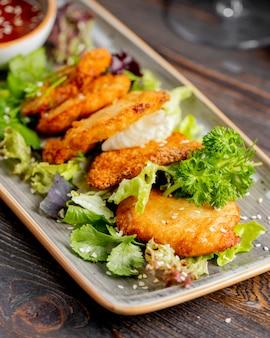 Escalope de poulet servie avec laitue et légumes verts