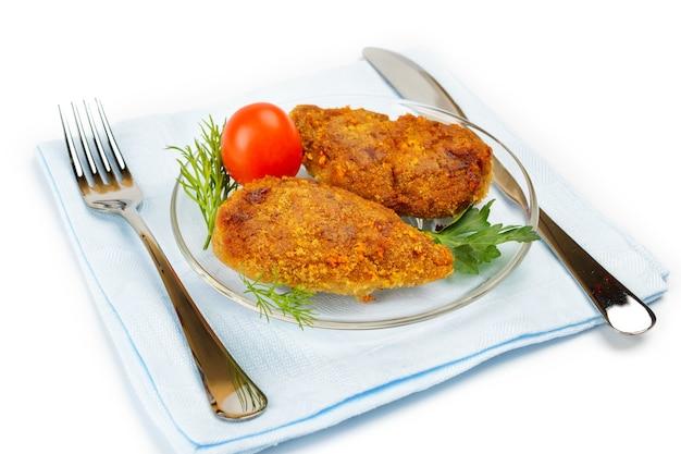 Escalope de poulet sur une serviette bleue. servir avec un couteau et une fourchette.