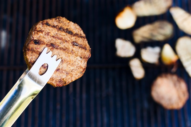 Escalope de viande grillée au forceps pendant le pique-nique