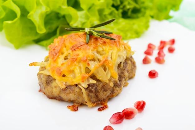 Escalope de viande juteuse, cuite au four avec des pommes de terre râpées et du fromage sur une assiette en céramique blanche. fermer
