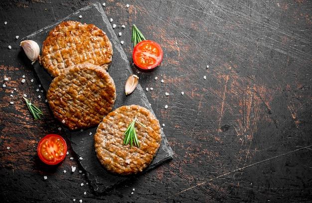 Escalopes à l'ail et une tomate en tranches sur une table en bois foncé