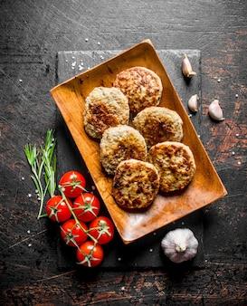 Escalopes sur une assiette en bois avec de l'ail, du romarin et des tomates sur une branche. sur rustique foncé