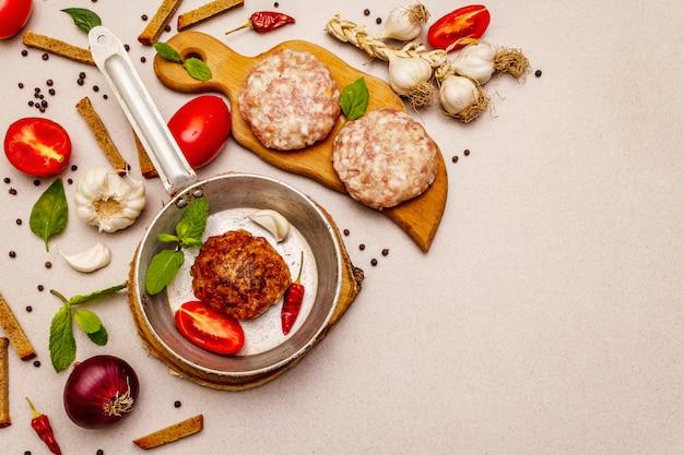 Escalopes crues et frites, légumes frais, épices, huile d'olive. concept de cuisson pan, pique-nique ou barbecue vintage