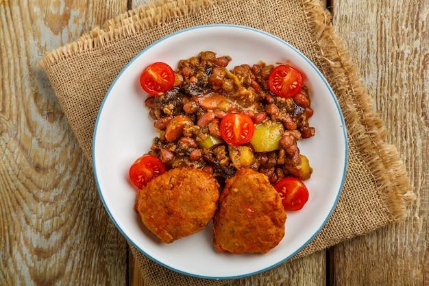Escalopes de morue avec compote de pommes de terre et légumes sur une assiette sur une serviette.