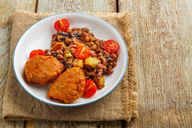 Escalopes de morue avec pommes de terre et légumes sur une assiette sur une serviette.