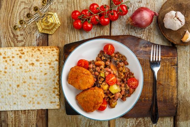Escalopes de morue avec pommes de terre et légumes sur un support rond à côté des ingrédients.