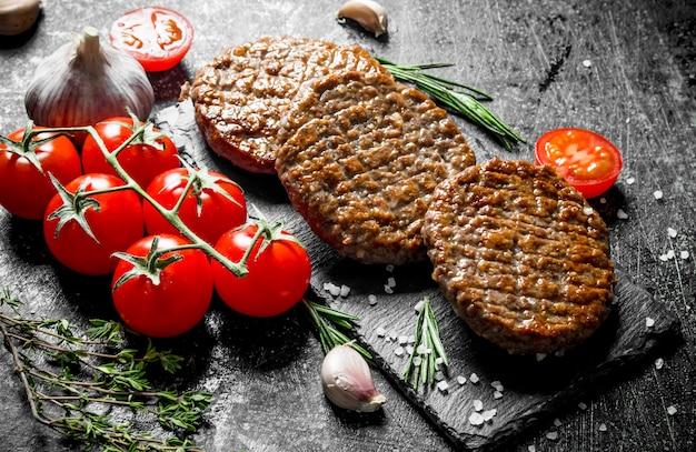 Escalopes sur une planche de pierre avec des tomates et de l'ail. sur fond rustique noir