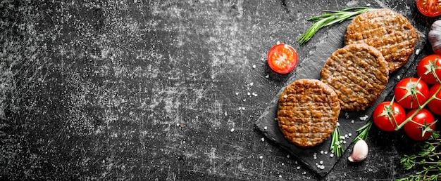 Escalopes sur une planche de pierre avec des tomates et de l'ail.