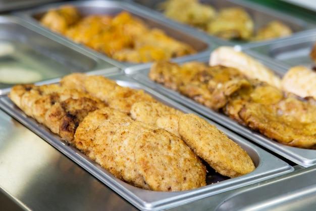 Escalopes et plats de viande au buffet sur des assiettes en métal. mise au point sélective