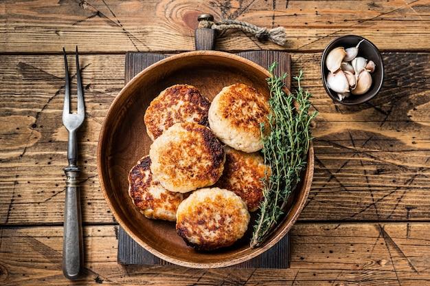 Escalopes de poisson rôties ou galette dans une assiette en bois. fond en bois. vue de dessus.