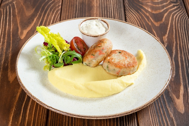 Escalopes de poisson à la vapeur avec purée de pommes de terre, légumes et sauce blanche sur table en bois