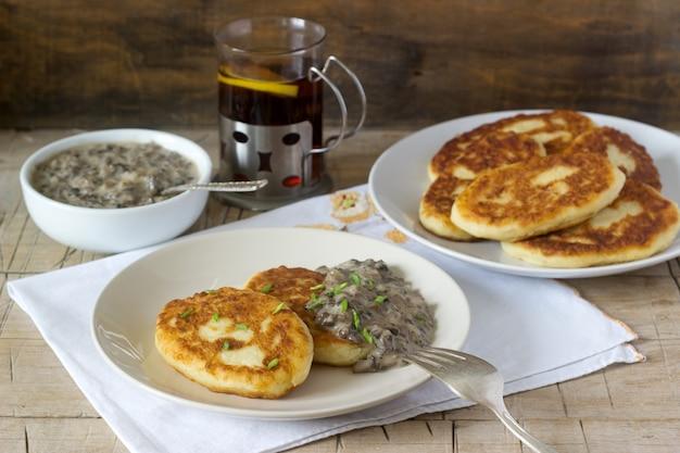 Escalopes de pommes de terre ou crêpes avec sauce aux champignons et oignons verts. style rustique.