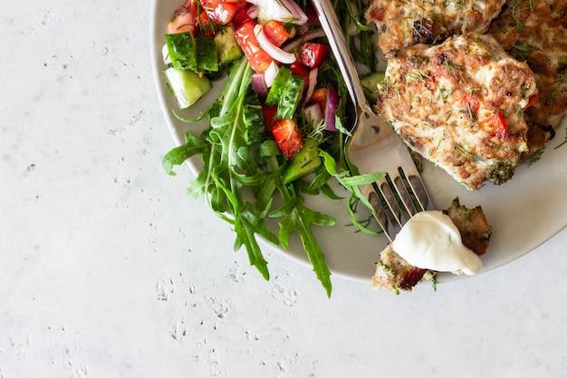 Escalopes de poulet ou de dinde avec légumes et sauce dans une assiette. délicieuses côtelettes avec salade.