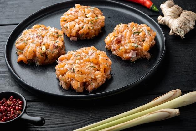 Escalopes de saumon asiatiques rapides crues, sur une table en bois noir