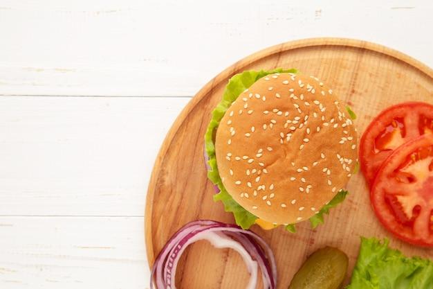 Escalopes de steak burger avec assaisonnement, fromage, tomates, salade et petit pain sur blanc. vue de dessus