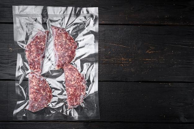 Escalopes de veau de boeuf dans un emballage en plastique sous vide, sur fond de table en bois noir, vue de dessus à plat, avec espace de copie pour le texte