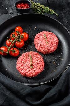 Escalopes de viande de bœuf hachée crue, galette dans une poêle