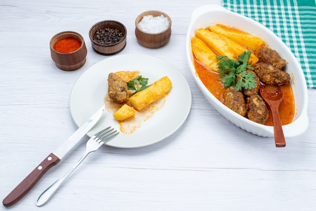 Escalopes de viande cuites avec pommes de terre en sauce et assaisonnements verts sur un bureau blanc, légume de viande de repas alimentaire