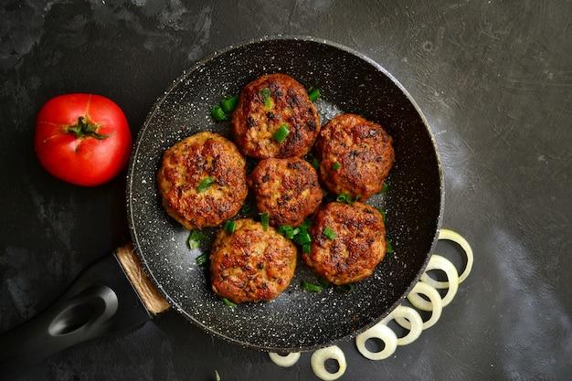 Escalopes de viande. escalopes dans une poêle sur une table en béton noir .. délicieux plats savoureux. vue de dessus