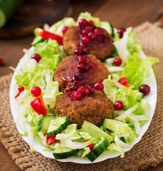 Escalopes de viande juteuse avec sauce aux canneberges et salade sur une table en bois dans un style rustique.