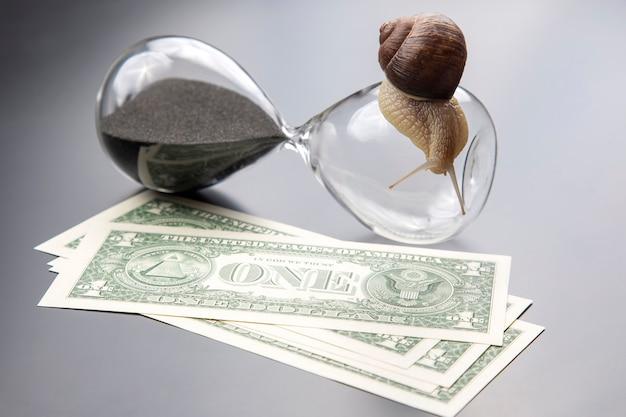 Escargot rampe sur un sablier contre l'argent