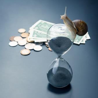 Escargot rampe sur un sablier dans le contexte de l'argent