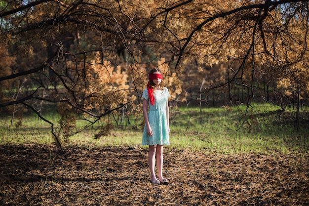Esclavage. très jolie jeune fille avec un ruban rouge les yeux bandés. apparence de poupée. femme aux cheveux bruns dans une robe turquoise sur la nature. cheveux longs. lumière naturelle. modèle posant sur la nature. enlèvement