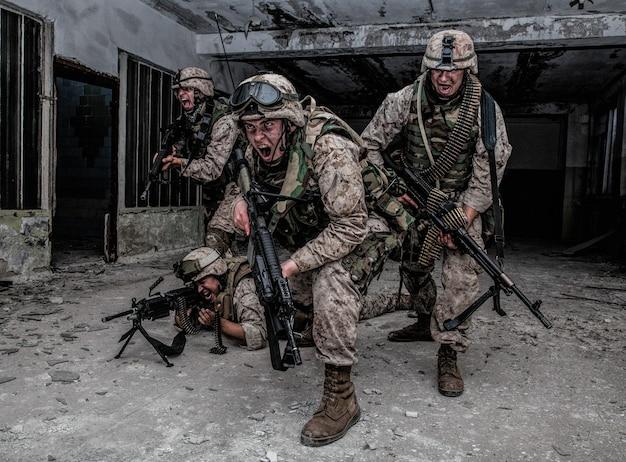 Escouade d'assaut des marines américains, détachement spécial de commando, équipe d'élite de l'armée armée d'une arme automatique, criant et attaquant l'ennemi, perçant le combat, se précipitant avec le feu lors d'un échange de tirs urbain