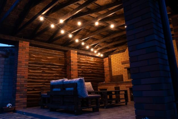 Espace barbecue le soir avec ampoules anciennes. meubles en bois et palettes.