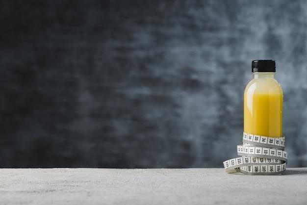 Espace boisson saine dans une bouteille de sport avec fond de ruban à mesurer alimentaire