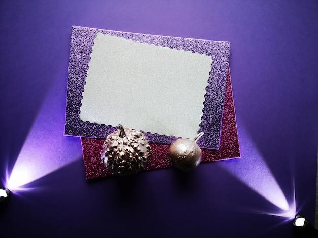 Espace copie sur des cartes en papier scintillant avec des citrouilles peintes en rose métallique et deux projecteurs sur fond violet foncé. fond d'halloween au néon