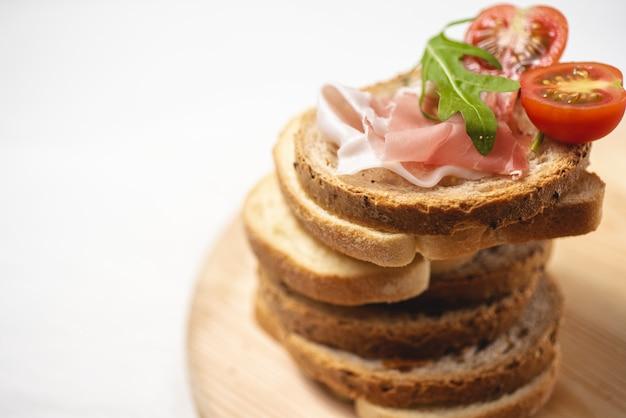 Espace copie, délicieux pain frais au jambon, tomates et salade de roquette sur planche de bois