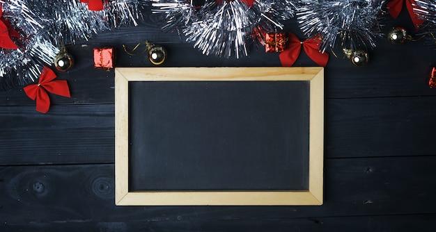 Espace de copie du tableau noir. ornement de noël argenté sur une planche de bois noire. vue de dessus