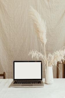 Espace copie espace ordinateur portable écran et pelucheux herbe de la pampa dans un vase élégant contre le mur de lin beige pastel