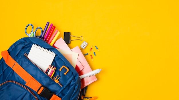 Espace copie jaune avec sac à dos rempli de fournitures scolaires