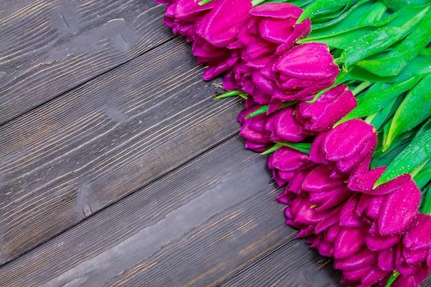 Espace copie de la journée de la femme avec des tulipes rose vif sur un fond en bois noir, textures