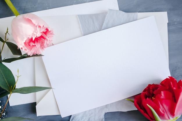 Espace de copie de papier vierge. cadre avec des fleurs. ruban de soie. fond gris. bouquet simple. carte de voeux.