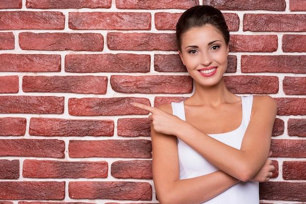 Espace de copie de pointage de beauté. portrait de belle jeune femme aux cheveux courts pointant vers l'extérieur souriant tout en se tenant contre le mur de briques