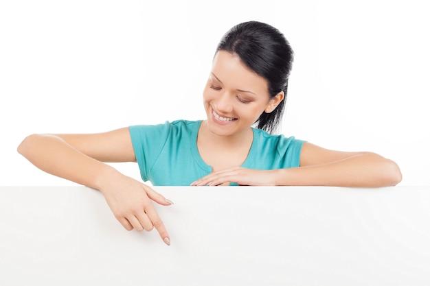 Espace de copie de pointage. belle jeune femme se penchant sur l'espace de copie et le pointant tout en isolé sur blanc
