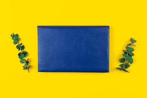 Espace de copie pour ordinateur portable en cuir bleu et cmposition de maquette avec fleurs séchées sur table de bureau, fond jaune, photo à plat et vue de dessus